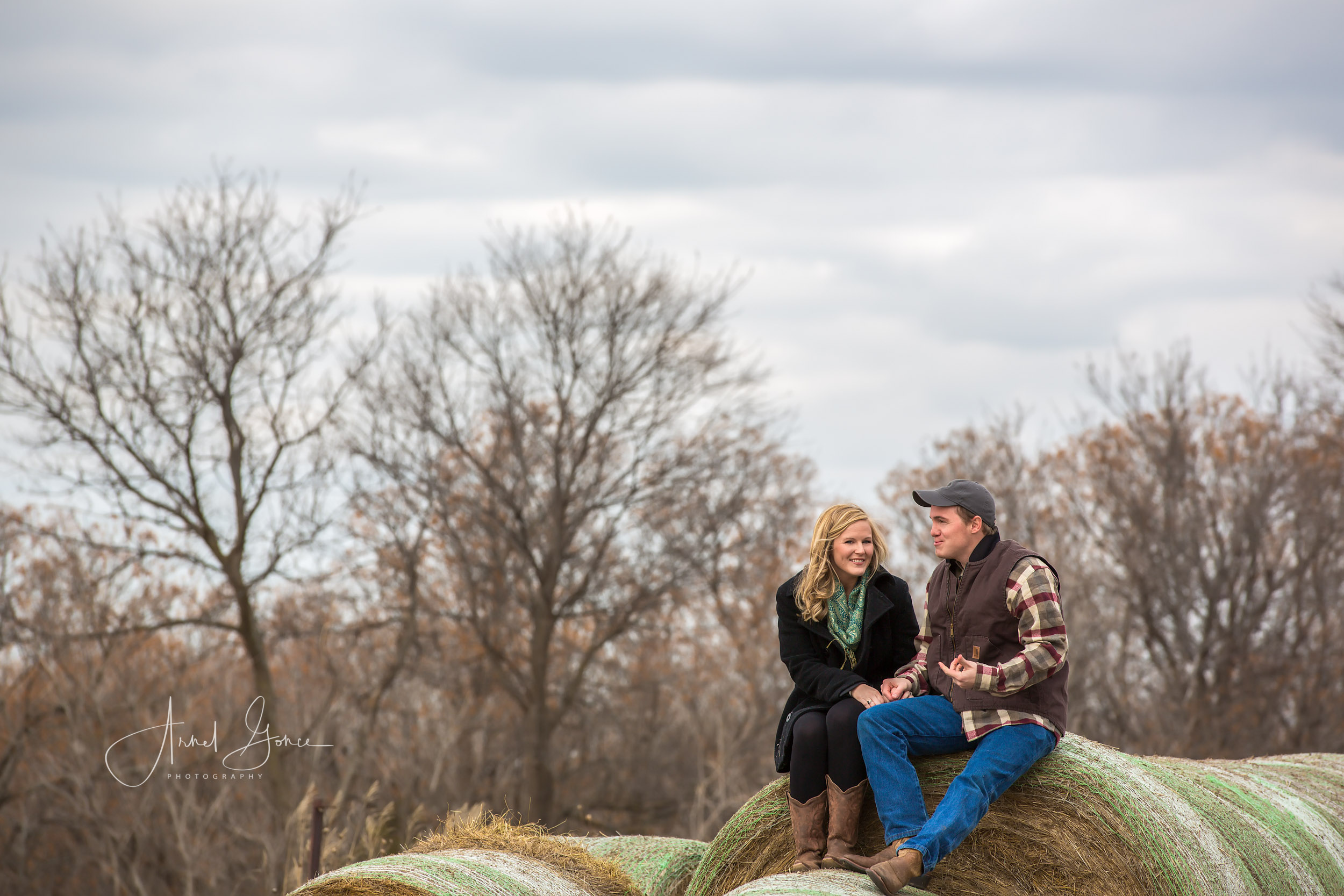 Man and woman sitting side by side on a bale of hay talking