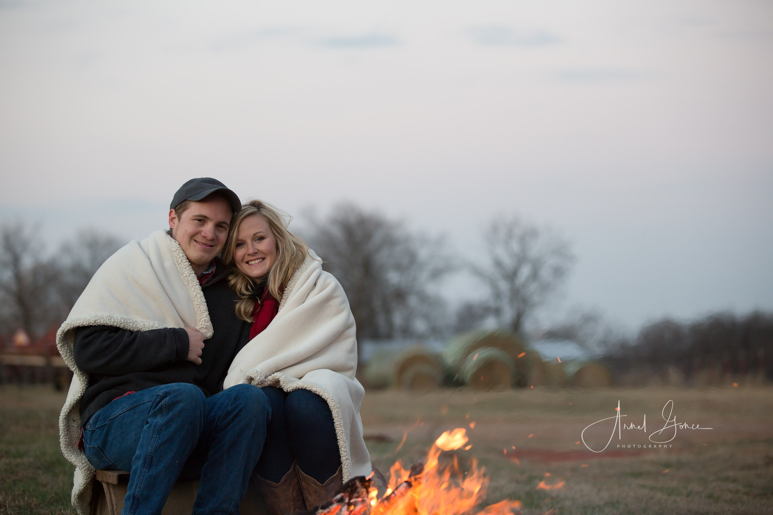 Couple snuggles under a blanket at a campfire for the last image of the engagement portrait session.